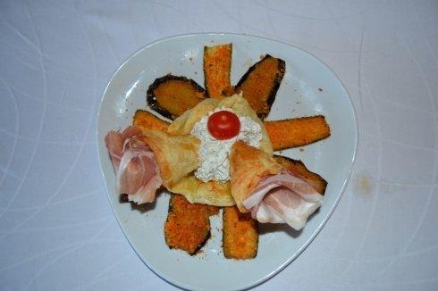 piatto con omlette pomodoro al centro e prosciutto
