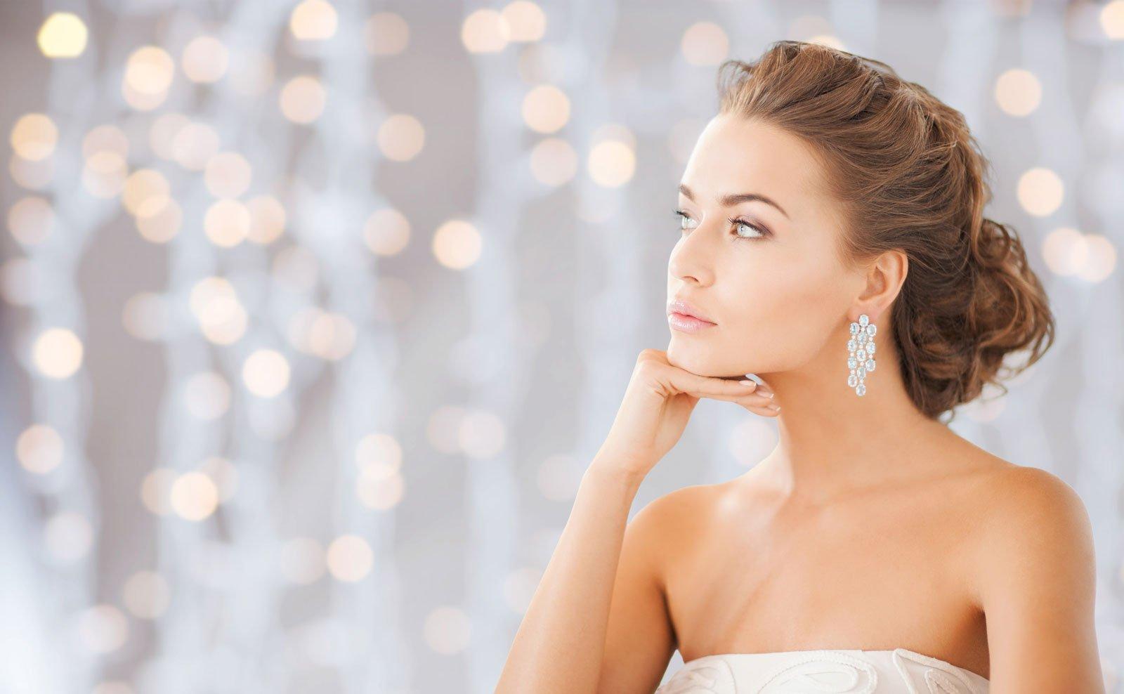 bella donna che indossa orecchini di diamanti lucidi su sfondo di luci