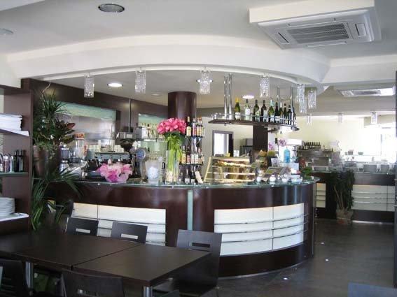 vista frontale di bancone di un bar nero e bianco con gelateria e veni in vetrina