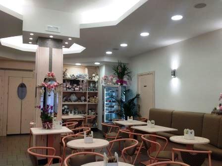 vista interna di un ristorante con tavolo e sedie, parete bianca e luce in soffitto