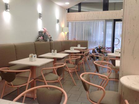 vista interna di ristorante con tavolo, sedie, tenda trasparente e arredamento