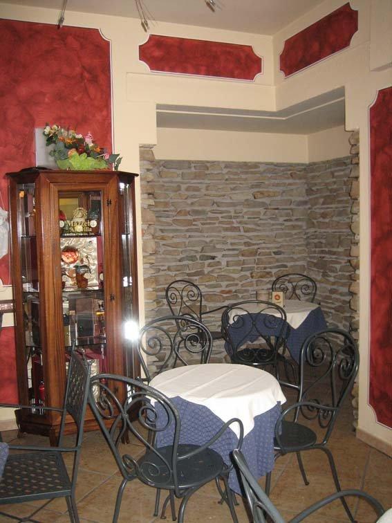 vista angolare di un ristorante con vetrina in legno e vetro, tavoli apparecchiati e sedie