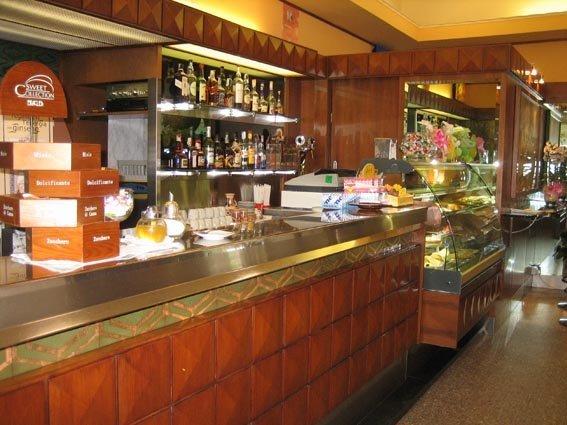 vista laterale di bancone in legno e gelateria di un bar