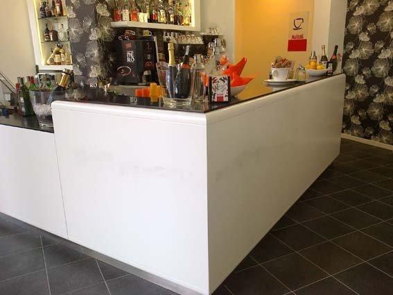 bancone di un bar ad angolo bianco con prodotti