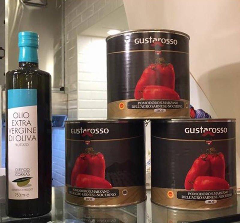 Scatole di salsa di pomodoro naturale e una bottiglia di olio d'oliva extra vergine