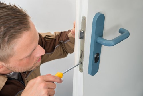 Service expert changing a lock in Rochester, NY