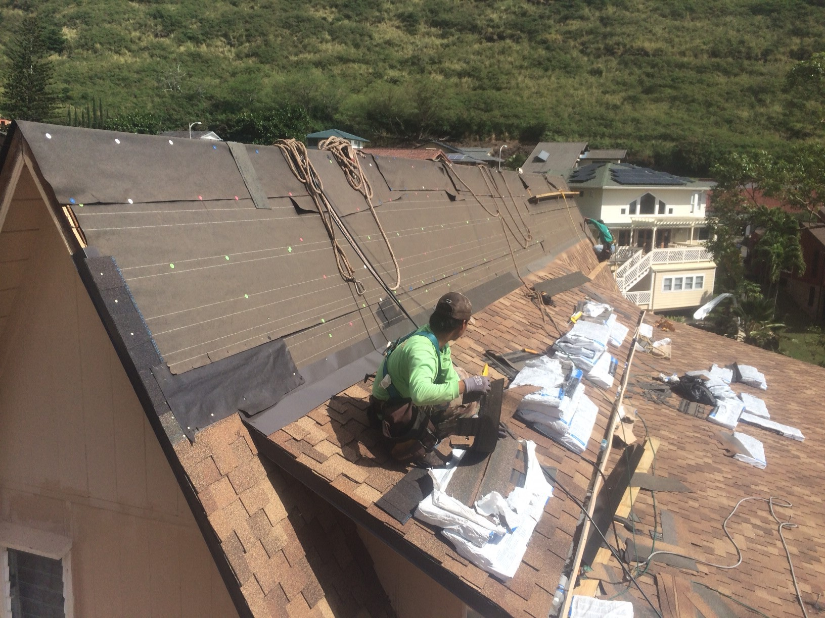 worker laying shingle roofing on Honolulu home