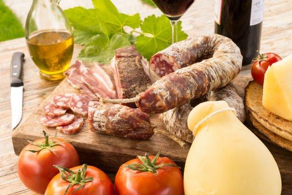 un tagliere con la salsiccia e accanto del formaggio e dell'olio di oliva