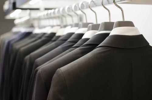 camicie e giacche da uomo in fila appese a grucce