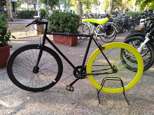una bici nera con una ruota nera e una gialla