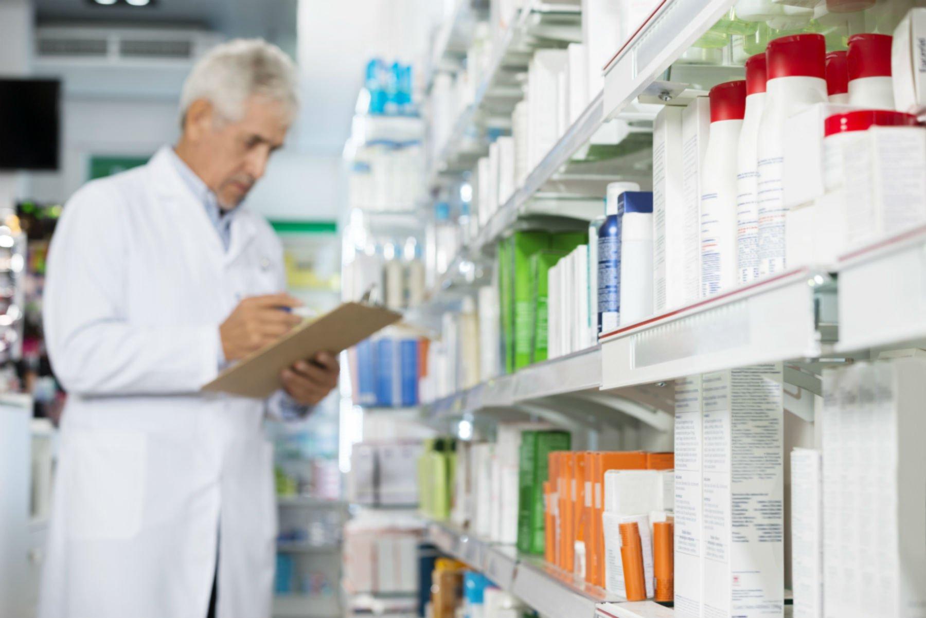 farmacista che controlla uno scaffale di medicinali