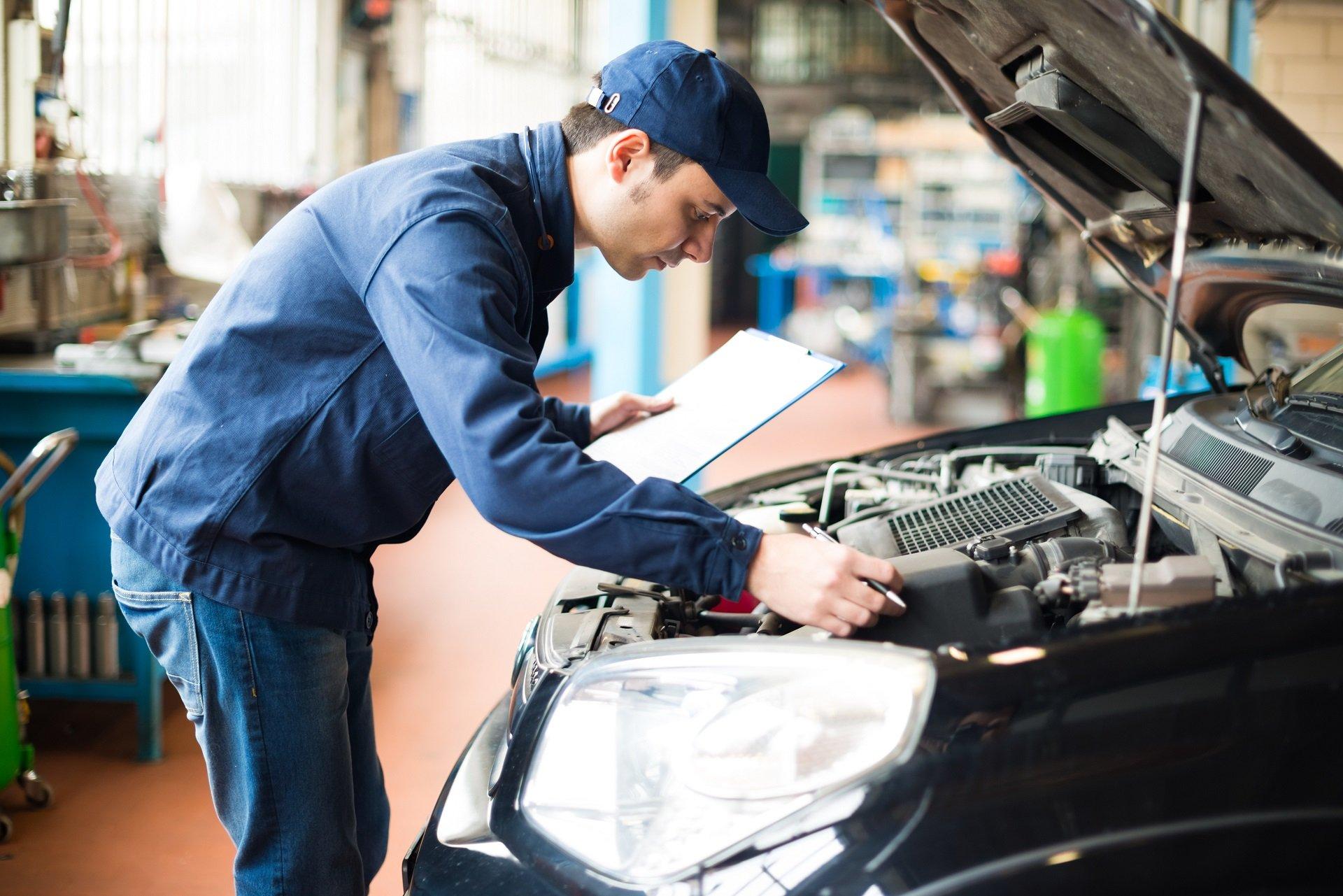 meccanico durante il controllo elettrico di un'auto