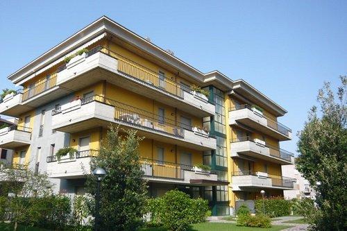uno stabile di color giallo con vista dei lunghi balconi