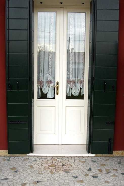 una porta finestra bianca con persiane verdi