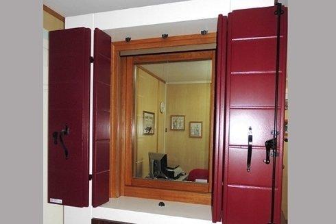 una finestra con infissi bordeaux in legno