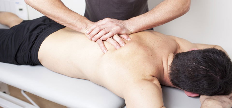 A therapist pressing his hands down on a male patient's back