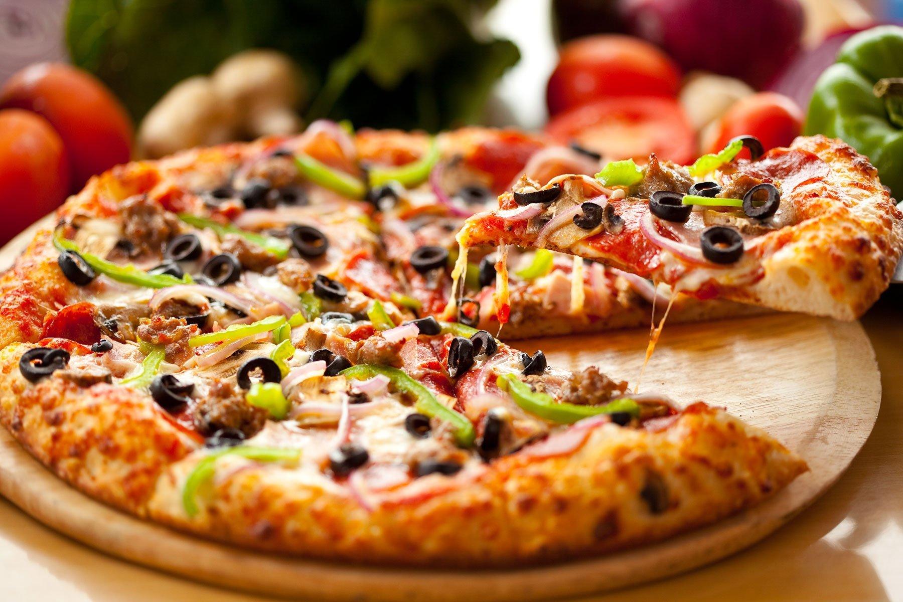 un tagliere di pizza con verdure e delle olive nere