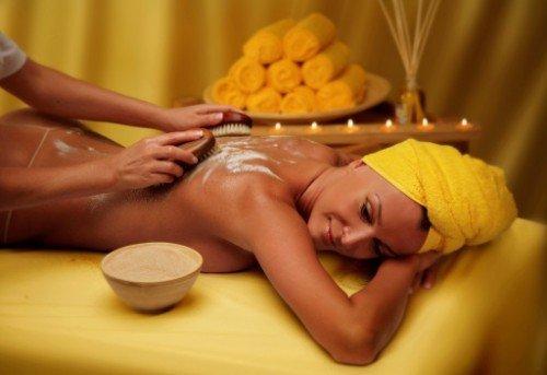 giovane donna su lettino durante trattamento corpo esfoliante