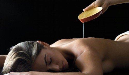 giovane donna su lettino durante candle massage
