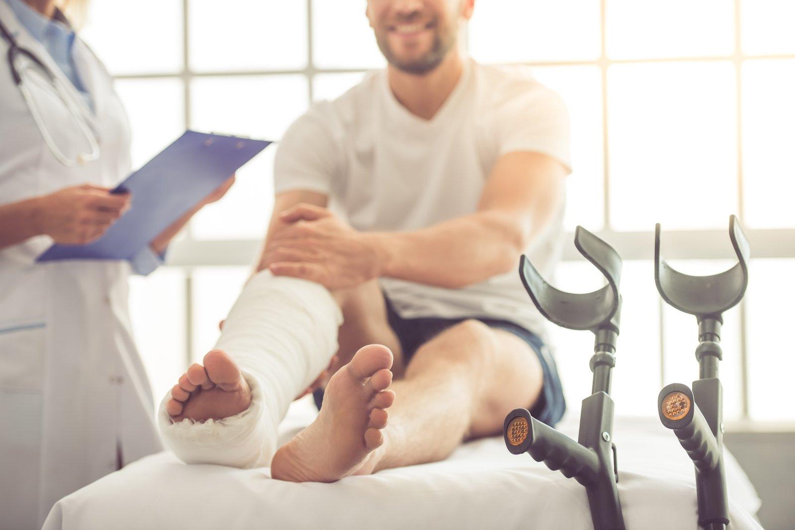 Bel medico femminile ascoltando il paziente con la gamba rotta e facendo note