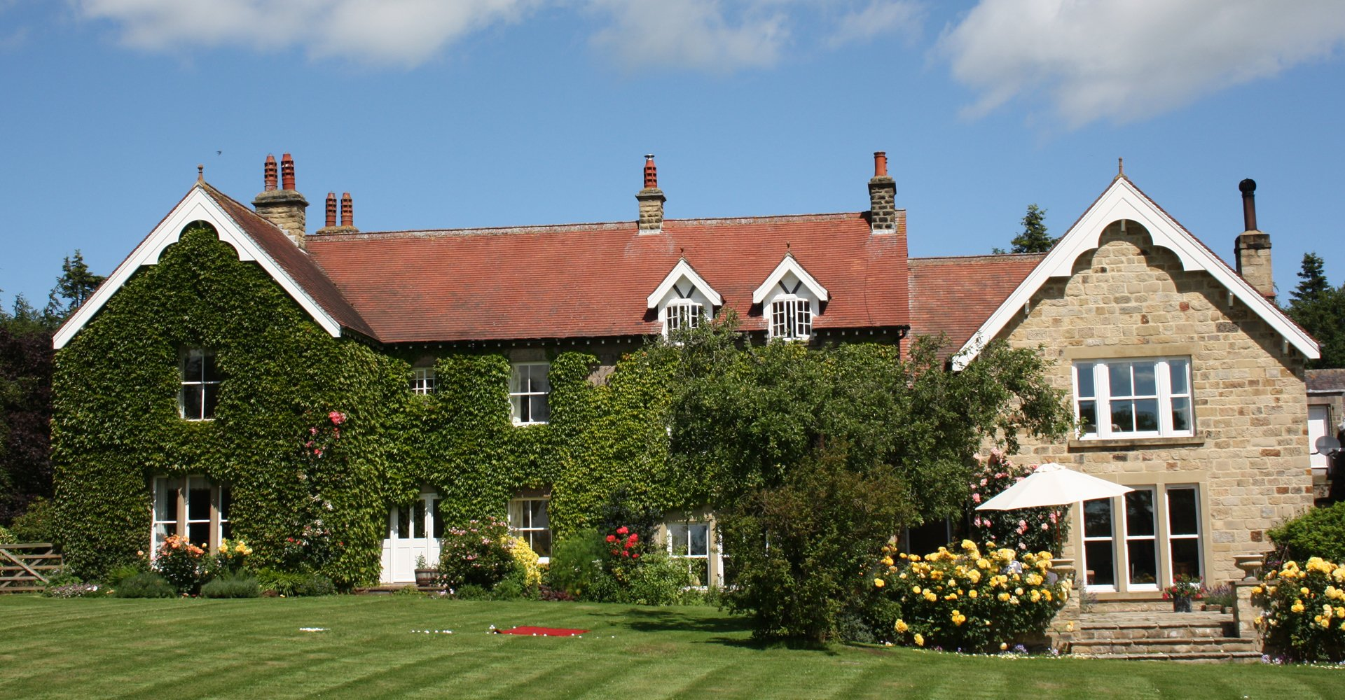 A large ivy-covered house with red roof and extension of pale brick, with a large lawn lined with trees and flowers