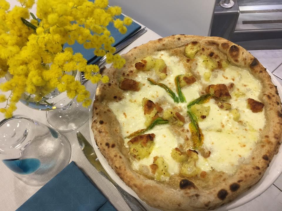 una pizza bianca con formaggio e accanto delle mimose