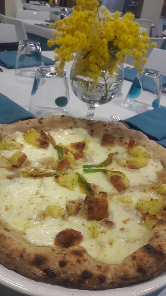 una pizza bianca con formaggio e delle mimose