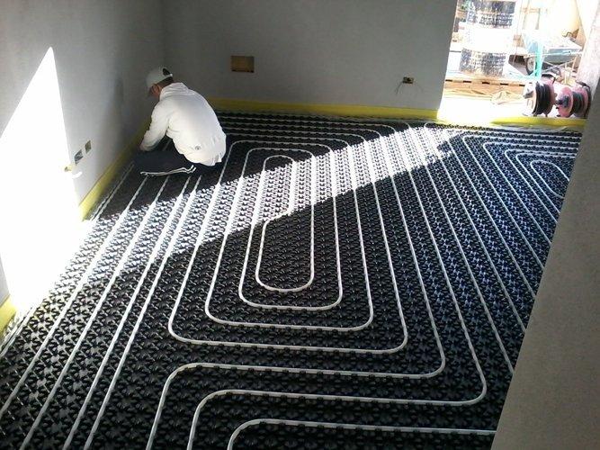 idraulico mentre lavora su un impianto a pavimento