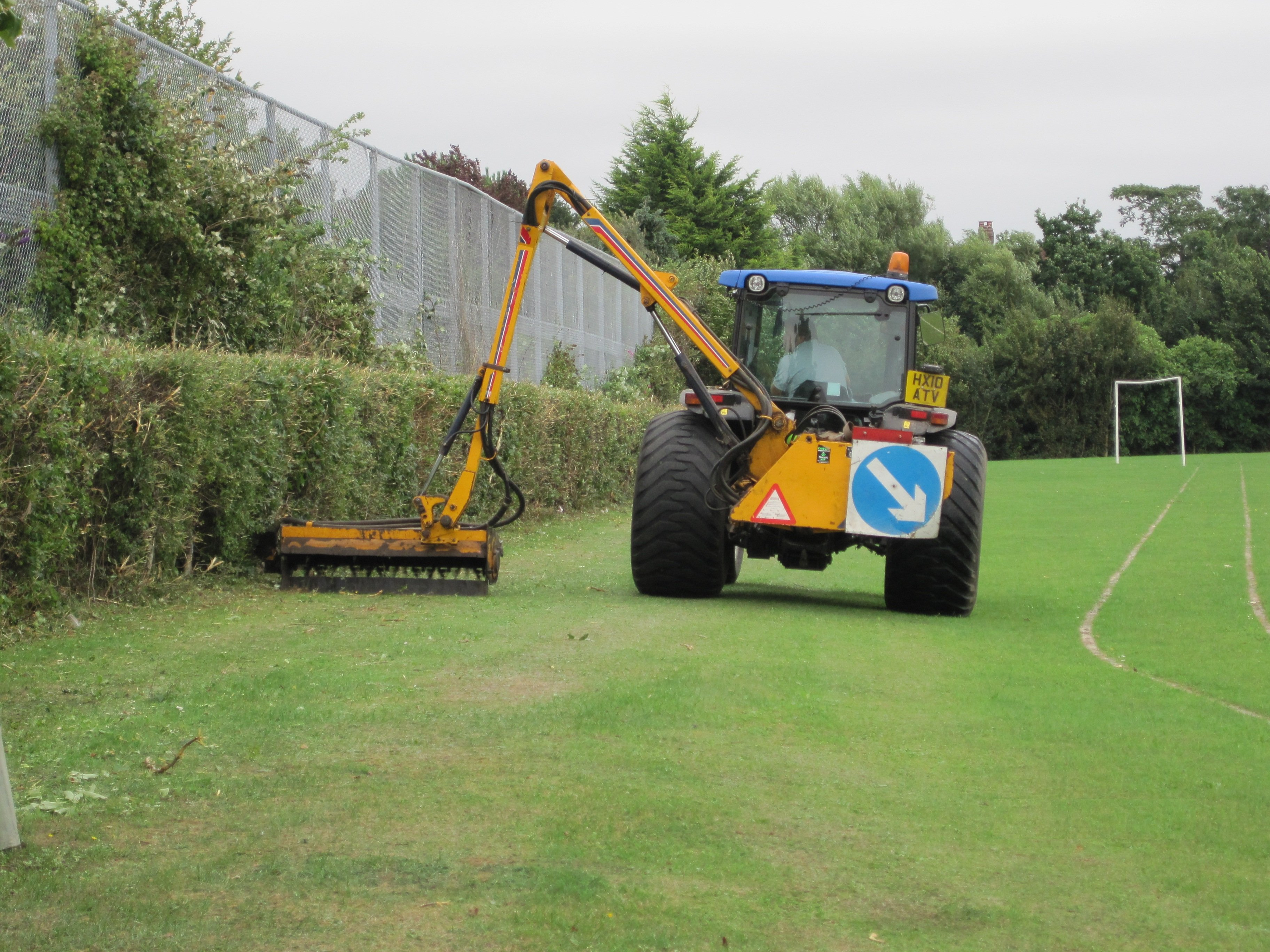 Tractor cutting a hedge