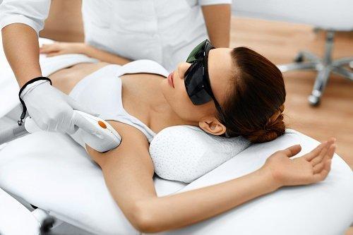 una donna sdraiata con degli occhiali protettivi neri e un'estetista mentre le depila le ascelle