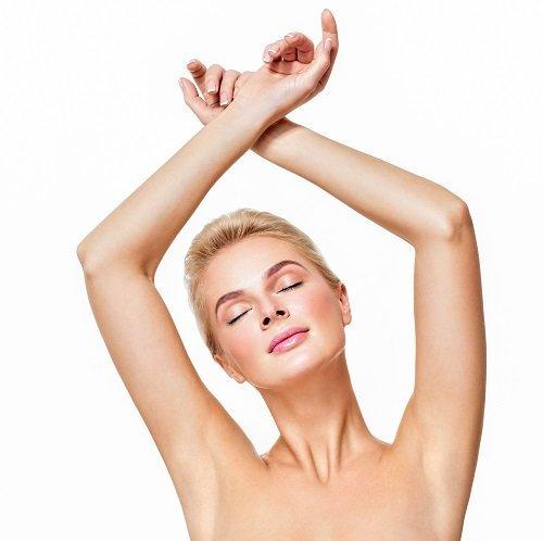 una donna con capelli corti biondi e con le braccia alzate