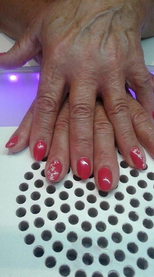 due mani con  dello smalto rosso sulle unghie