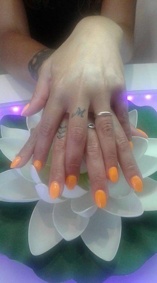 due mani con  dello smalto arancione sulle unghie