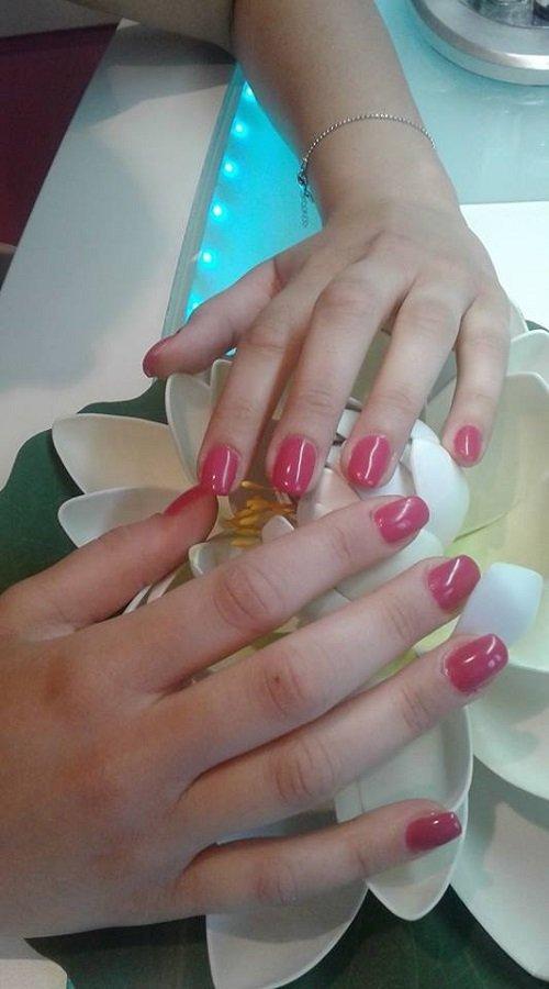 due mani con  dello smalto fucsia sulle unghie