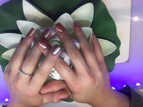 due mani con  dello smalto grigio sulle unghie