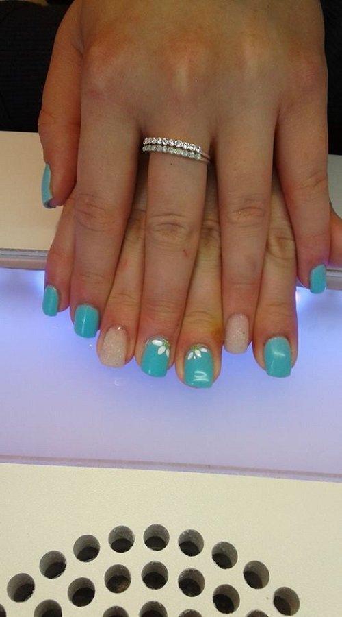 due mani con  dello smalto azzurro sulle unghie