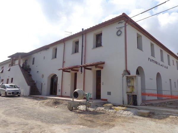 una betoniera e dietro uno stabile con facciata bianca