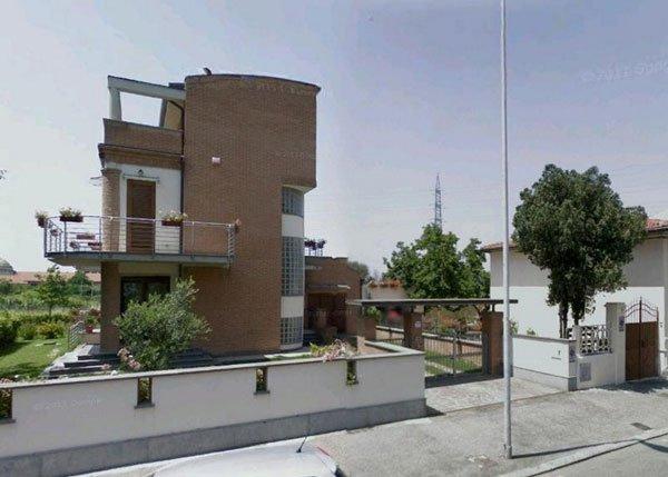 una villetta moderna con giardino e vista di un cancello