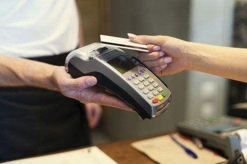 Donna che porge la carta di credito per passarla dal terminale e pagare
