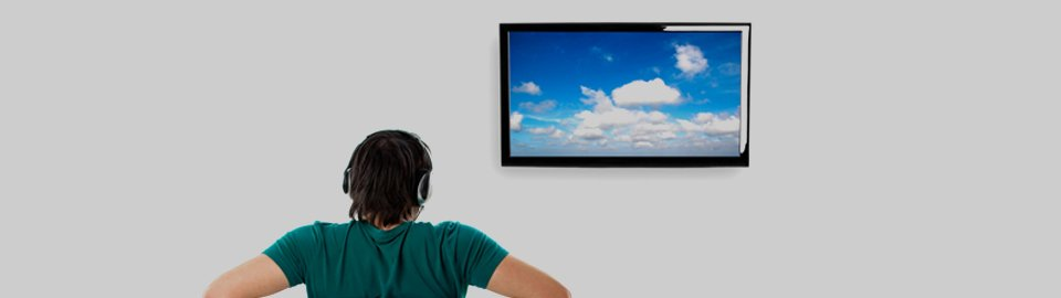 A man wearing headphones, facing a wall-mounted TV with blue sky and clouds on the screen