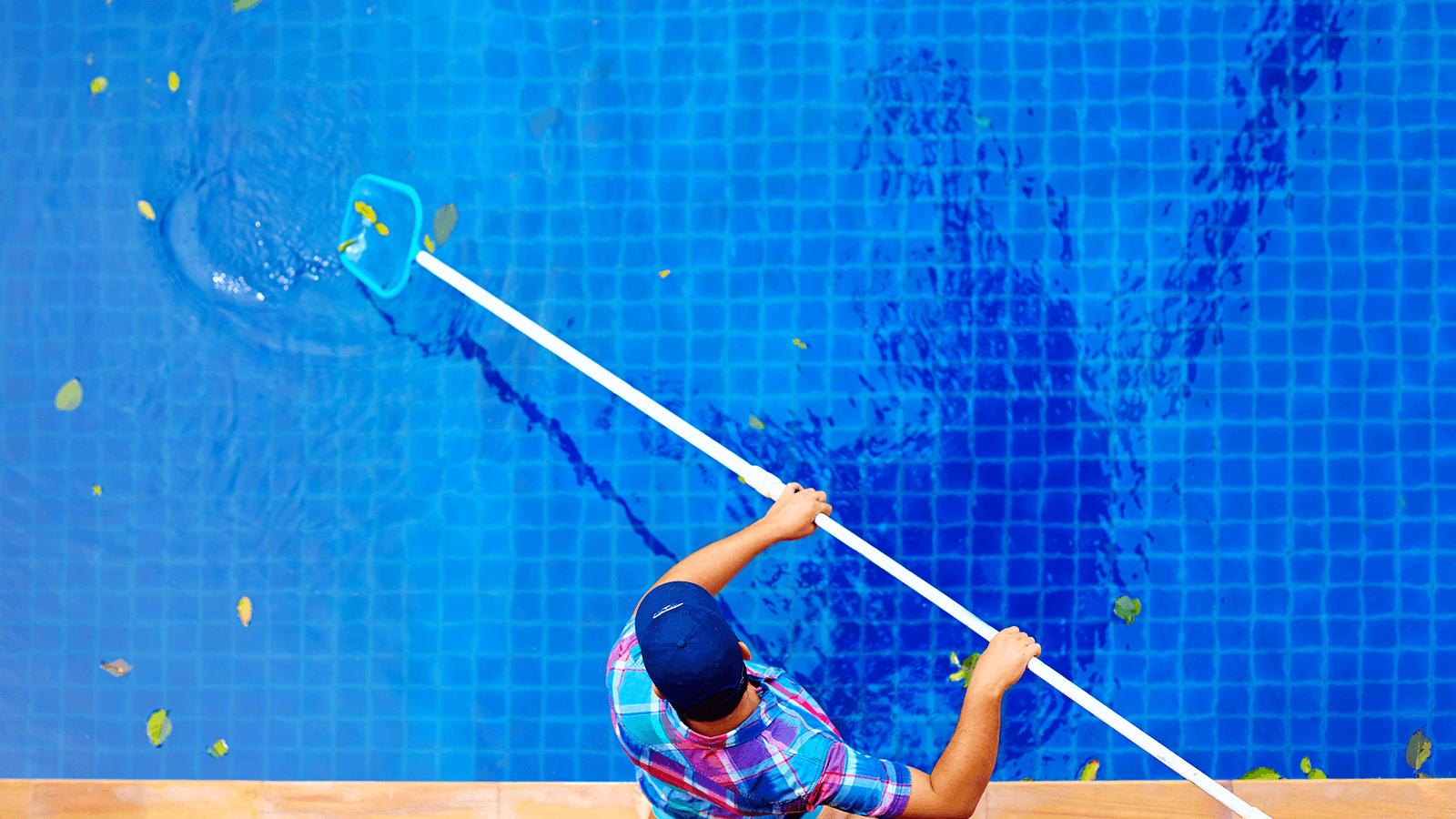 un uomo che pulisce una piscina con un retino