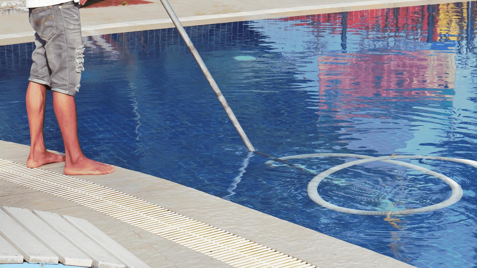 un uomo che pulisce una piscina