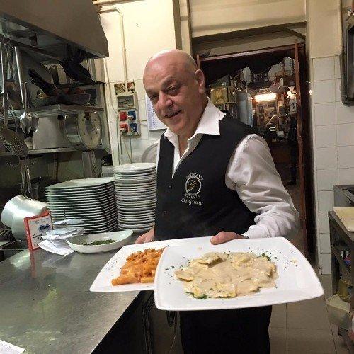 Il padrone con due pizze, una con mozzarella e l'altra con peperoni