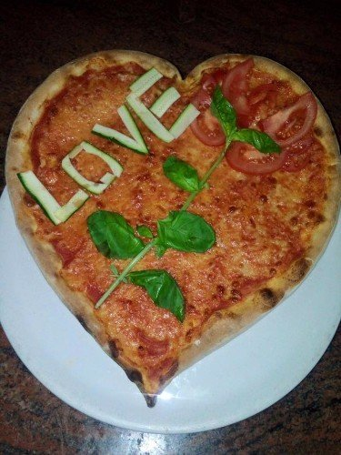 Pizza in forma di cuore con pomodori freschi e la scritta Love