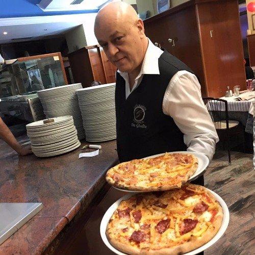 Il padrone con due pizze, una con mozzarella e l'altra, l'altra con peperoni