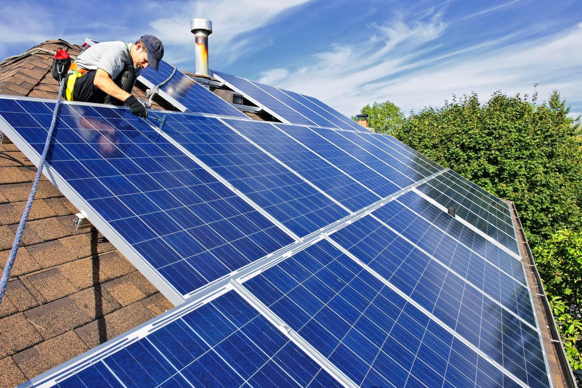 un uomo che installa dei pannelli solari su un tetto