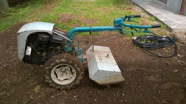 un macchinario da giardino con delle ruote e un manubrio