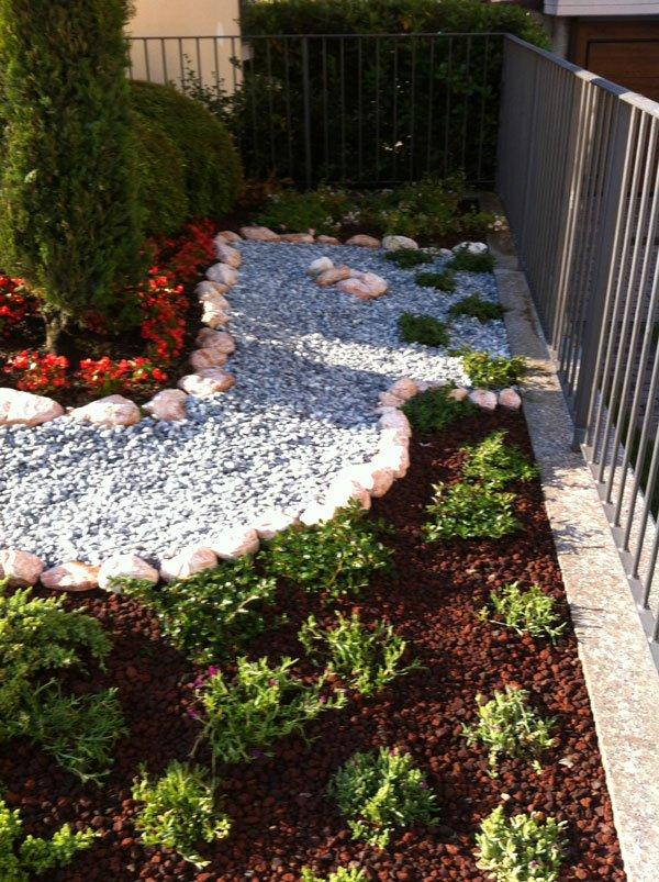 un'aiuola di sassolini, delle piantine e dei fiori rossi vicino a un alberello