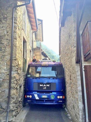camion in mezzo a due edifici in pietra