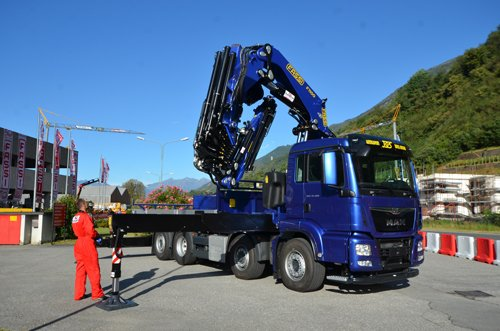 operaio in tuta da lavoro e camion con braccio meccanico